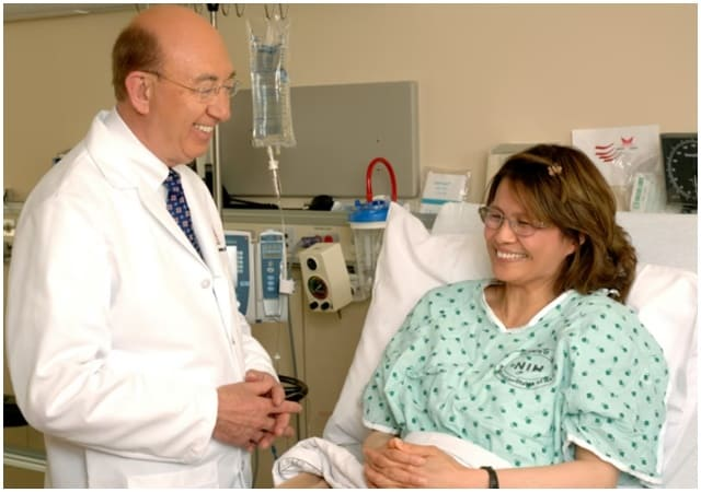 A doctor talking to a patient  Description automatically generated with medium confidence