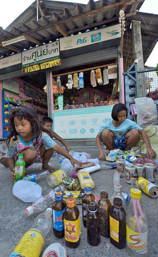 Thai children selecting used bottles and cans before trading them