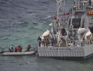 U.S. Navy salvage assessment team members board the stern of USS Guardian