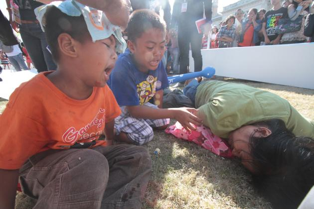 A 35-year-old mother and her two young sons were injured at Government House yesterday when a wooden arch erected as part of National Children's Day festivities collapsed on them.