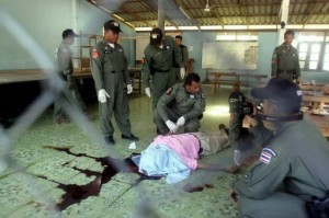 Police inspect the body of a Muslim teacher at a school cafeteria in Thailand's Narathiwat province