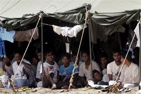 Rohingya refugees sit in their encampment at a military base