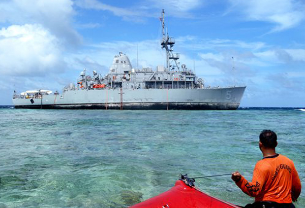 In this Jan. 22, 2013 photo released by the Philippine Coast Guard, coast guard divers approach the USS Guardian, a U.S. Navy minesweeper, to assess the situation after it ran aground last week off Tubbataha Reef, a World Heritage Site in the Sulu Sea, 640 kilometers (400 miles) southwest of Manila, Philippines. A U.S. Navy official said the USS Guardian has been punctured and taking in water and has to be lifted off the rocks