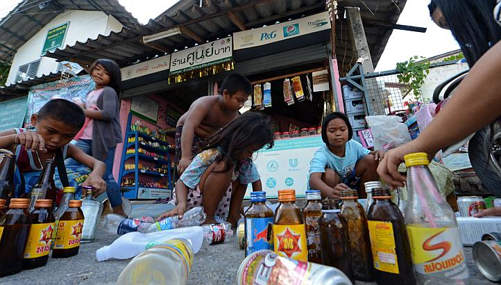 """Children select used bottles and cans before trading them at a """"zero baht shop"""" in Bangkok"""