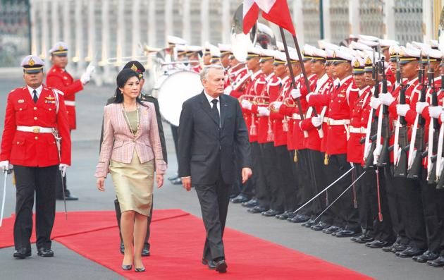 French PM Jean-Marc Ayrault reviews a guard of honour at Government House yesterday, prior to a meeting with his Thai counterpart Yingluck Shinawatra.
