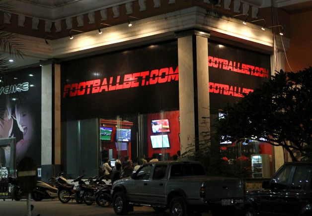 People watch the live soccer matches at an online gambling shop in Poipet