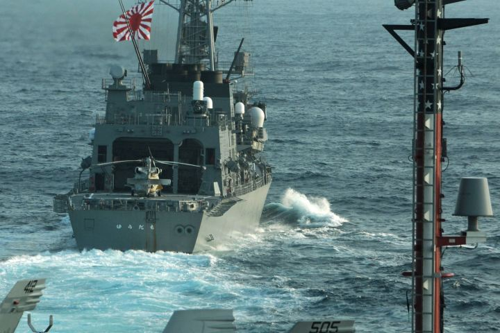 Japan Maritime Self Defense Force destroyer JS Yudachi sails in formation with the USS George Washington, foreground, during exercises in the East China Sea last year. Japan says a Chinese warship locked targeting radar onto the Yudachi in the same region