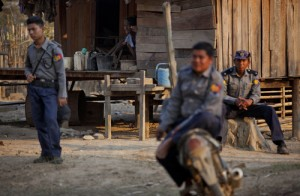 ethnic Lisu man looks out of his house as Myanmar police officers watch a gathering of villagers in Thon Min Yar village, central Shan state, Myanmar.