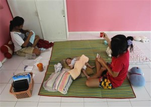 An un-named 16-year-old teenager (R) rest with her one-month-old son at the Association for the Promotion of the Status of Women in Bangkok