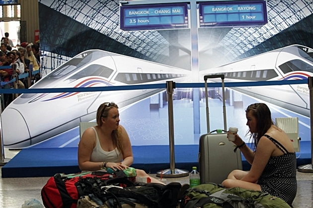 Tourists chat in front of a billboard display of high-speed trains at Hua Lamphong railway station in Bangkok