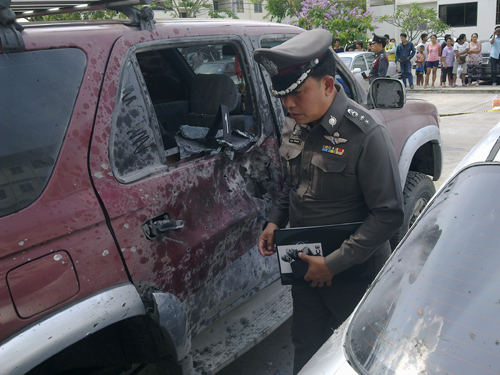 Police inspect the car damaged by a handgrenade explosion that killed a man at an apartment building car park in Lat Krabang
