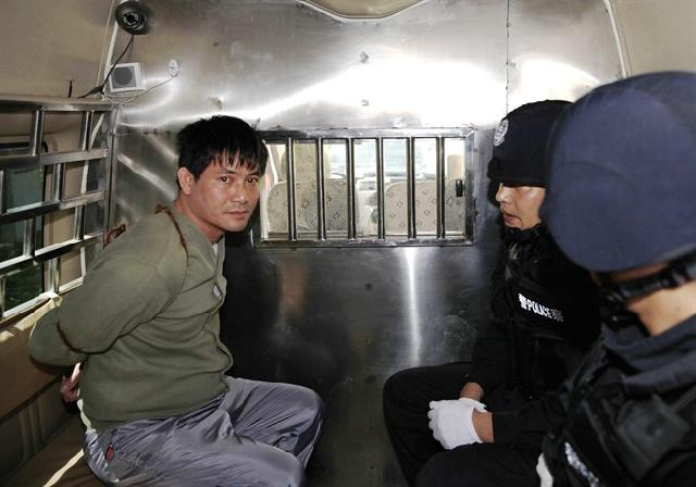 In this photo released by China's Xinhua News Agency, Myanmar drug lord Naw Kham, left, sits in a police van before being taken execution chambers in Kunming, capital of southwest China's Yunnan Province, Friday, March 1, 2013 - See more at: http://www.calgaryherald.com/news/China+executes+foreigners+over+Mekong+River+murders+following/8033198/story.html#sthash.vvehpJQM.dpuf