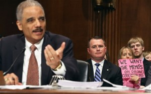 Eric Holder, left, testifies before the Senate Judiciary Committee as Code Pink demonstrator Medea Benjamin protests against the use of drone strikes