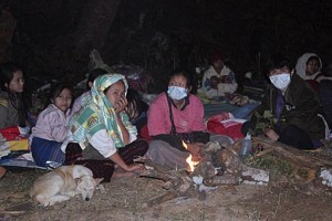 Karen refugees take shelter on the road near the Ban Mae Surin refugee camp after the fire burnt down their thatch huts in Mae Hong Son province