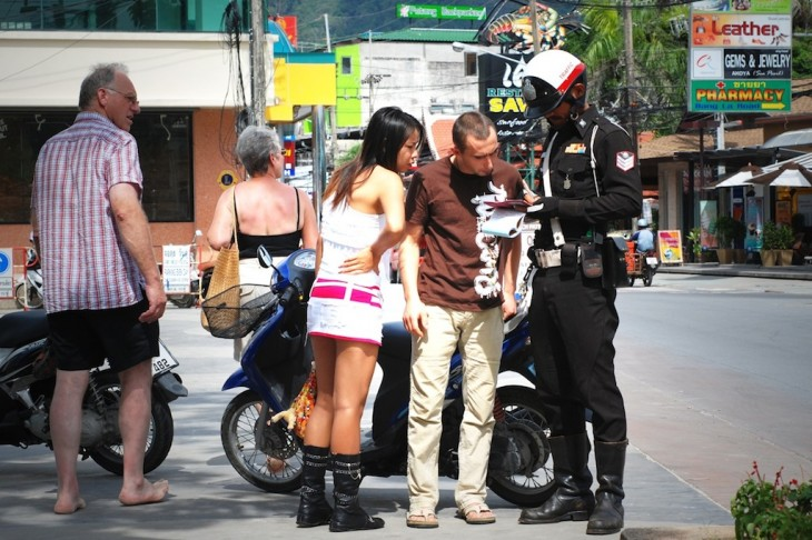 A Phuket police officer hands out tickets to tourists for riding bikes without helmet. William Cho / Flickr
