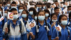 Thai schoolchildren wear masks and march on the street in an anti-burning campaign