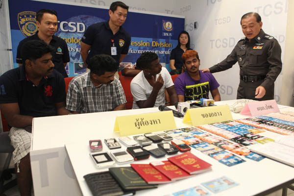 Four suspects (seated) and the seized items are shown by the police