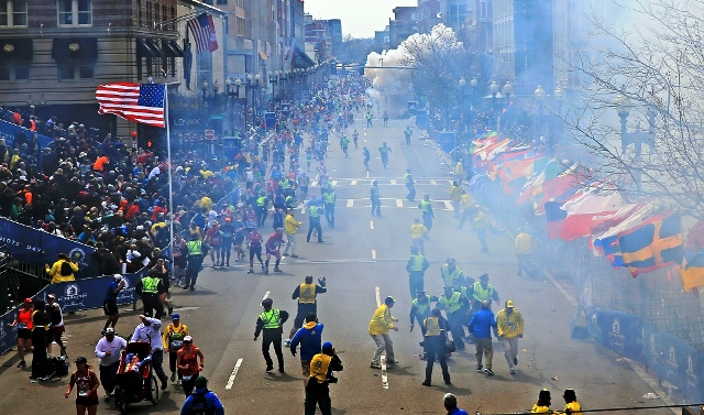 People react as an explosion goes off near the finish line of the 2013 Boston Marathon in Boston