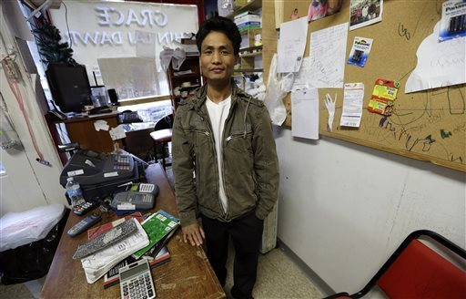 Ngun Za Bik stands at the front counter of his Grace Chin Store that once housed a pizza restaurant, in Columbus Junction, Iowa, on Wednesday, April 17, 2013. Bik arrived in Indianapolis in 2008 after living in the Malaysian jungle for 14 years. He struggled to make a living, working part-time at a warehouse. He relocated to Columbus Junction, where his brother was already working at Tyson, to open the store.