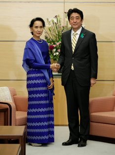 Nobel laureate and Myanmar opposition leader Aung San Suu Kyi (L) shakes hands with Japan's Prime Minister Shinzo Abe
