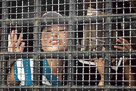 North Korean woman looks out from a caged prison van