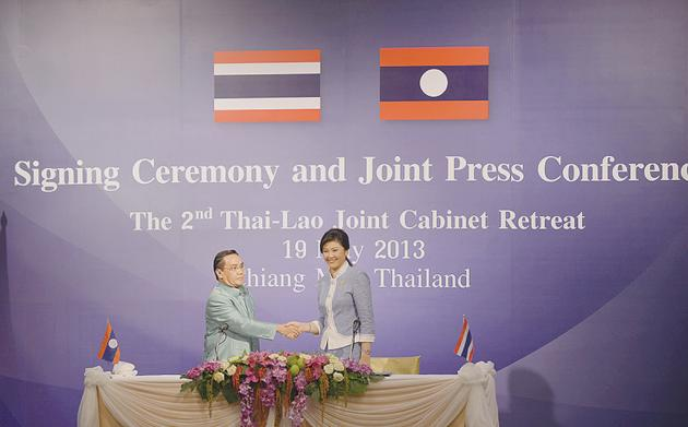 A government handout photo shows Thai Prime Minister Yingluck Shinawatra, right, shaking hands with Lao Prime Minister Thongsing Thammavong during the second Thai-Lao Joint Cabinetmeeting in Chiang Mai yesterday.