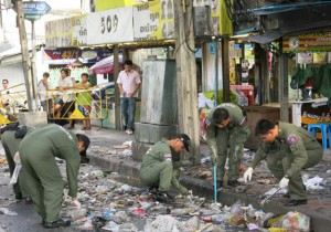 Police explosive ordnance disposal officers on Monday morning inspect the damage caused by an apparent bomb explosion at the entrance of Ramkhamhaeng Soi 43/1 on Sunday nigh