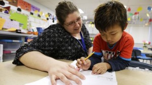 Roundy Elementary School kindergarten teacher Jennifer Young works with student Nang Zam Lian, in Columbus Junction