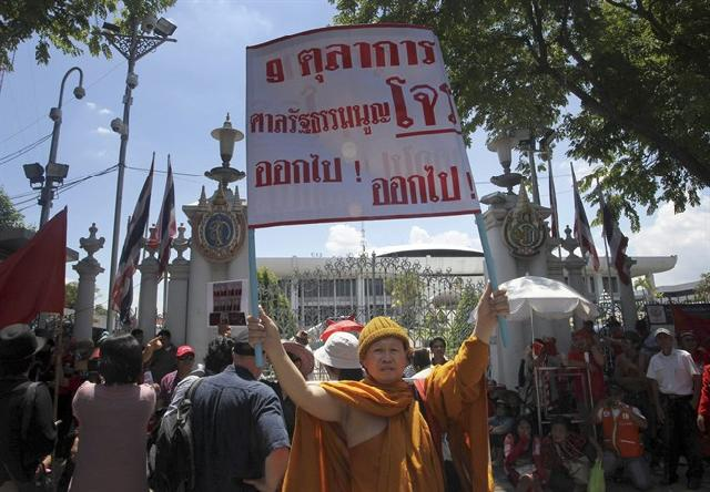 """A Buddhist monk holds up a placard reading """"All the nine judges out"""" during a protest against the Constitution Court Wednesday, May 8, 2013 in Bangkok, Thailand. Hundreds of Red Shirt supporters took part in the protest demanding the resignation of the Constitution Court's judges, after their decision last month to review a proposed amendment to the constitution"""