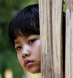 Karen girl peers from her bamboo hut at Mae La refugee camp in Ta Song Yang district of Tak province, northern Thailand.