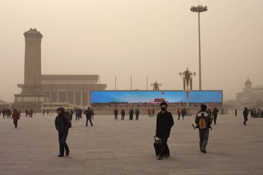 A giant screen on Tiananmen Square shows an image of Tiananmen Gate under a blue sky as part of a propaganda video on a polluted day in Beijing in February. Recruitment consultants say it is becoming harder to attract top talent to China — both expats and Chinese nationals educated abroad — because of the chronic pollution