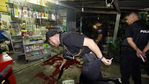 Thai security personnel inspect a grocer's shop where six people were shot dead by suspected Muslim militants in the southern province of Pattani