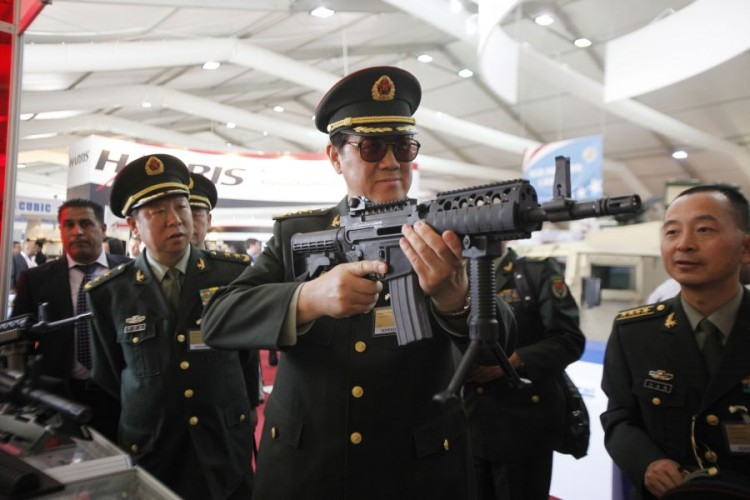 Chinese officers examine rifles of ARES Defense Systems, Inc from the U.S. during the 9th Special Operations Forces Exhibition and Conference (SOFEX), May 8, in Amman, Jordan