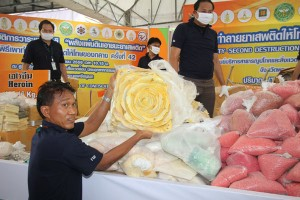 Officials help prepare the drugs for burning