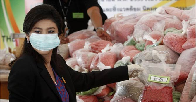 Thailand's Prime Minister Yingluck Shinawatra holds bags of methamphetamine during Destruction of Confiscated Narcotics ceremony