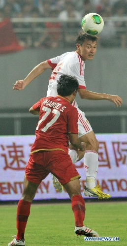 China's Gao Lin (Top) vies with Thailand's Phairod Sokham during their friendly soccer match in Hefei