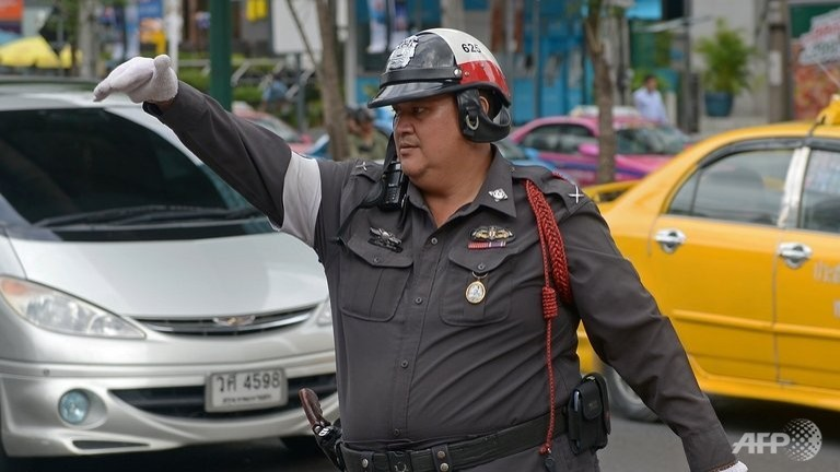 A policeman directs traffic on a street in Bangkok