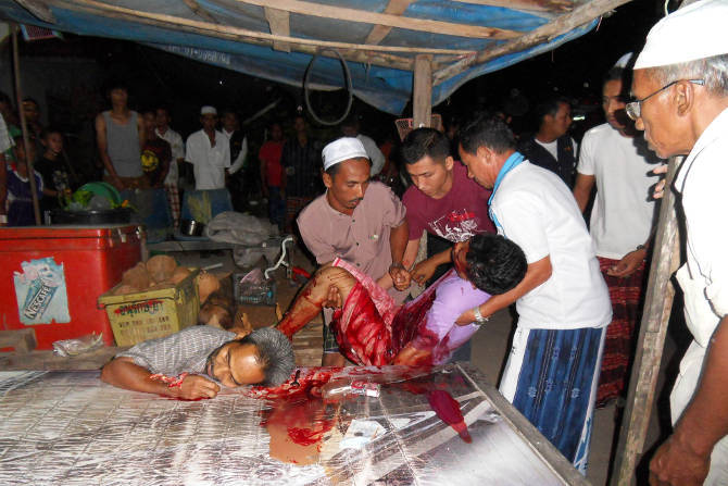 Onlookers watch as the bodies of Awae Nisaya (right), 38, and Maseng Moong, 42, are removed from a teashop in Lubo Bersa, Narathiwat. Two unidentified assailants armed with an assault rifle allegedly shot both men to death Tuesday