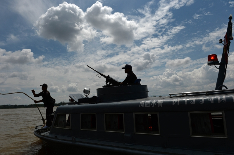 Policemen from the Thai Marine Border Police patroling along the Mekong river, which marks the border between Thailand and Laos in Chiang Saen, northern Chiang Rai province, aboard a machine-gun-mounted armored boat. Photo courtesy