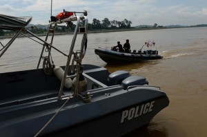Policemen from the Thai Marine Border Police patroling along the Mekong river, which marks the border between Thailand and Laos (background) in Chiang Saen, northern Chiang Rai province. Photo courtesy: