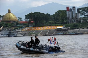 Policemen from the Thai Marine Border Police patroling along the Mekong river, which marks the border between Thailand and Laos (background) in Chiang Saen, northern Chiang Rai province