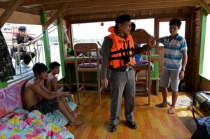 A policeman from the Thai Marine Border Police speaking to the Laotian crew of a boat after police went onboard as part of a patrol along the Mekong river, which marks the border between Thailand and Laos in Chiang Saen, northern Chiang Rai province