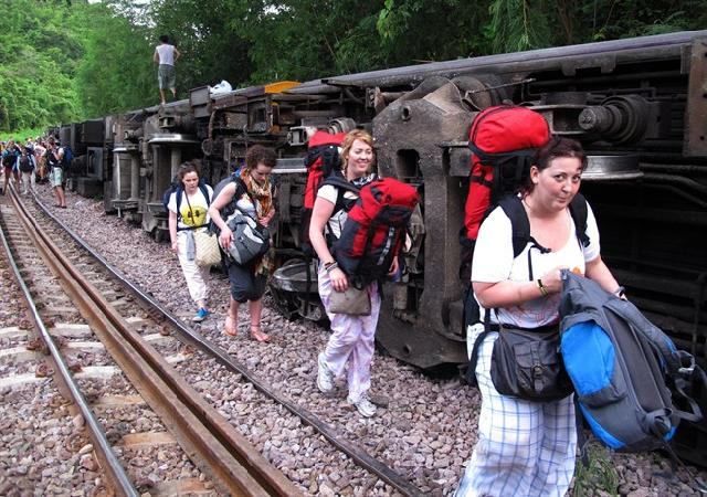 Passengers carry their belonging as they leave form a derailed train in Phrae province, northern Thailand