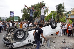 Angry Cambodians on top of an overturned police car next to a polling station in Phnom Penh