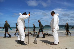 Pollution Control Department officials collect samples of sand from Ao Phrao beach on Koh Samet