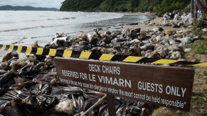 A resort signage is seen as Royal Thai Navy personel (background) clean up a beach from a major oil slick on Ao Phrao beach on the island of Ko Samet.