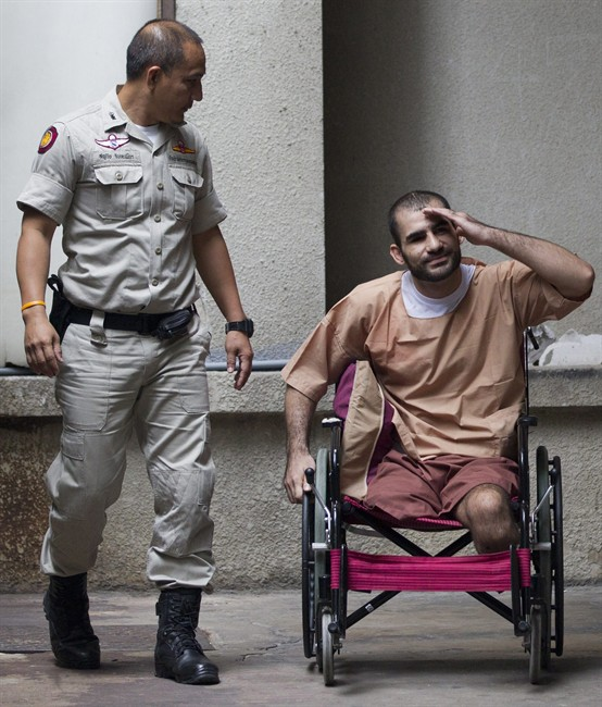 Saeid Moradi, an Iranian suspect bomber right, leaves the criminal court in Bangkok, Thailand, Thursday, Aug. 22, 2013. A Thai court sentenced Thursday, Moradi, 29, to life in prison for attempting to murder a police officer and possessing explosives that damaged property and injured several civilians