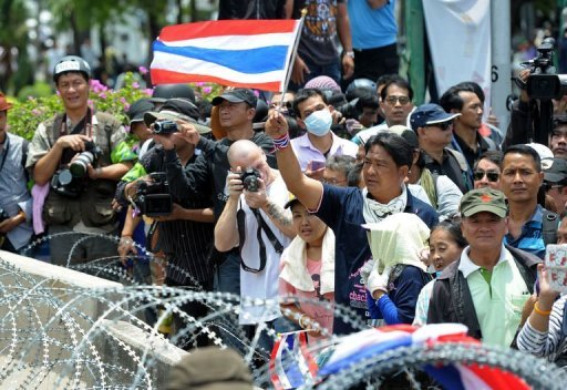 Anti-government protesters wave Thai flags next to barbed wire during a demonstration in Bangkok
