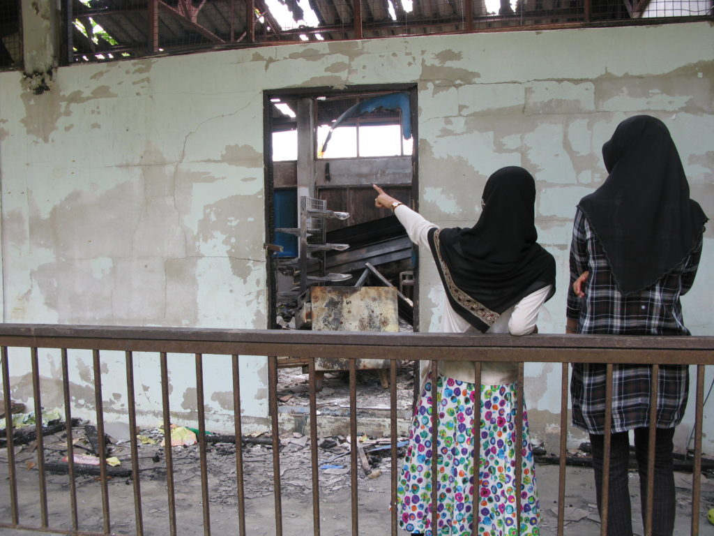 Two teachers inspect the damage at Ban Ba Ngo Elementary School, Pattani, Thailand