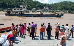 People wait to catch a boat to a casino complex in Laos from Chiang Rai in Thailand